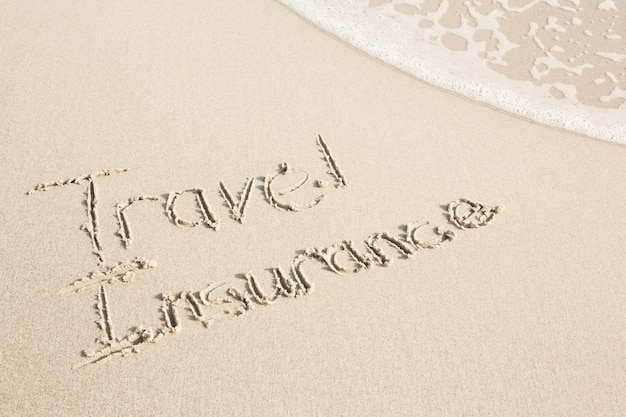 Travel insurance escrito na areia