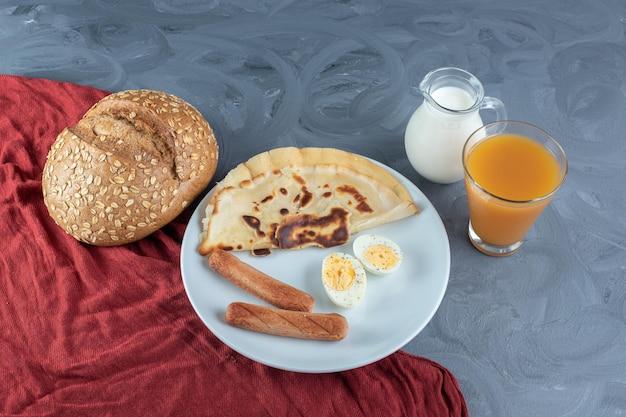 Travessa com panqueca, salsichas e rodelas de ovo cozido junto ao leite, sumo e pão numa superfície de mármore.