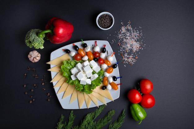 Travessa com queijo, tomate e azeitonas, em preto com tomate, endro, alho, pimenta verde e brócolis