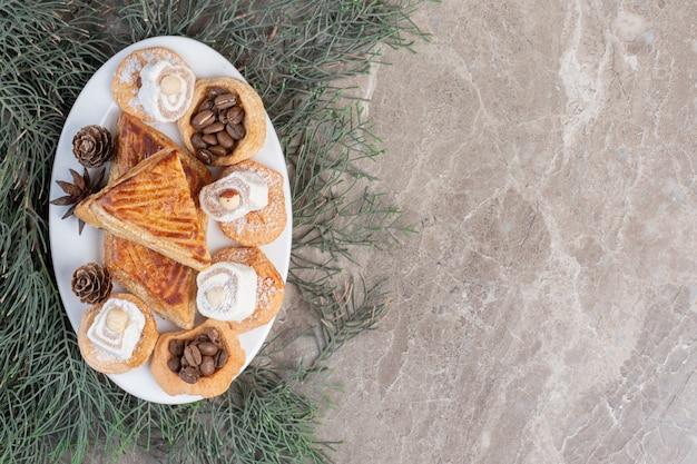 Travessa de massa com biscoitos, delícias turcas e kyatas em folhas de pinheiro sobre mármore.