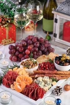 Travessa de petiscos variados de iguarias de salame e queijo, grissini envolto em presunto de parma, azeitonas e frutas cítricas. um antipasto original para uma festa de natal.