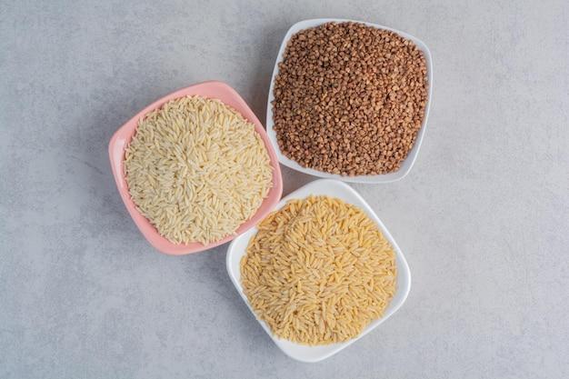 Travessas de arroz e trigo sarraceno na superfície de mármore