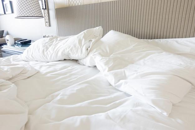 Travesseiro branco com cobertor na cama desfeito
