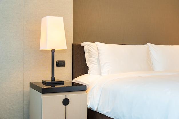 Travesseiro branco confortável e cobertor na cama com lâmpada de luz