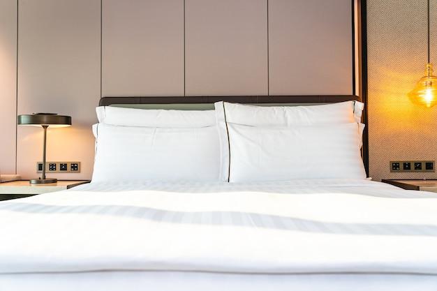 Travesseiro branco confortável e cobertor na decoração da cama no interior do quarto
