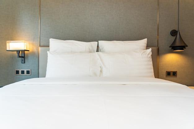 Travesseiro branco confortável na decoração da cama no interior do quarto