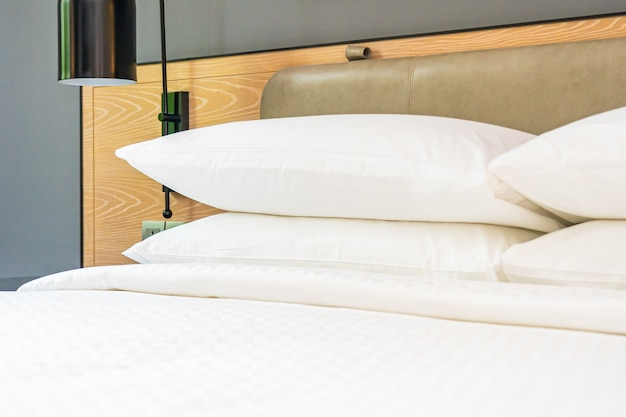 Travesseiro branco e cobertor na decoração da cama no interior do quarto