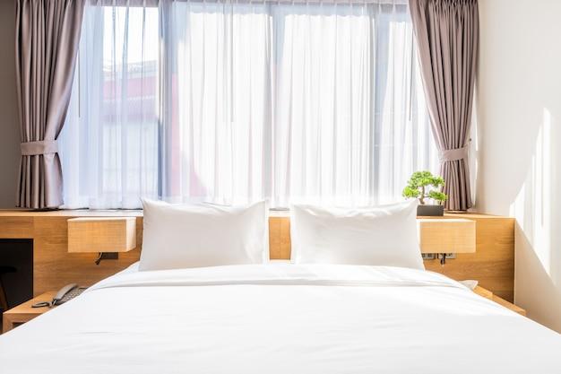 Travesseiro branco na cama decoração com luz da lâmpada e árvore verde em vasos no quarto de hotel