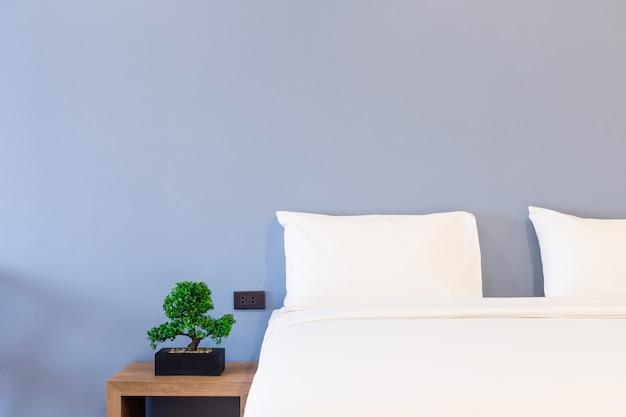 Travesseiro branco na cama decoração com luz da lâmpada e árvore verde em vasos