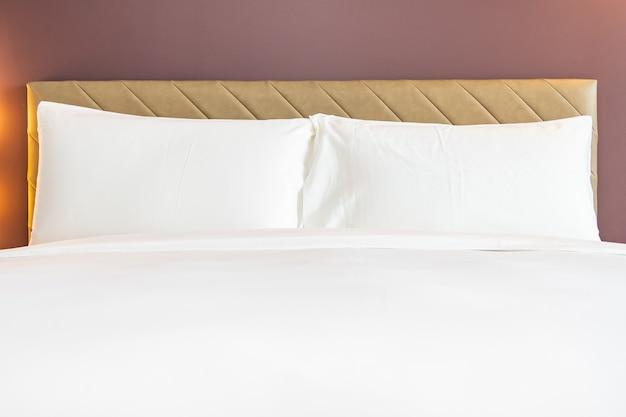 Travesseiro confortável de cor branca e cobertor na cama