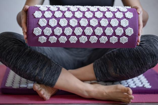 Travesseiro de acupuntura de massagem roxa e dicas de massagem branca nas mãos femininas.