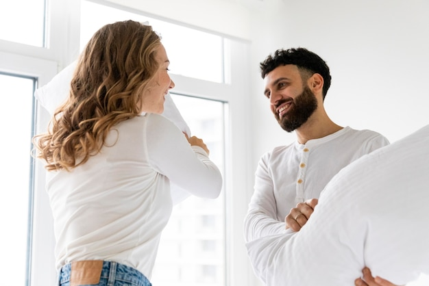 Travesseiro de casal sorridente brigando em casa