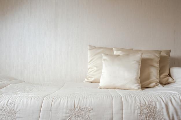 Travesseiro e cobertor de seda contra a parede creme do quarto, estilo moderno e luxuoso