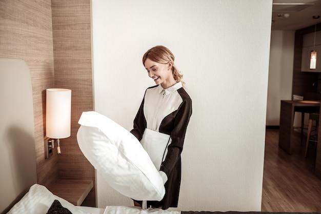 Travesseiro grande e confortável. empregada de hotel alegre segurando um grande travesseiro branco confortável depois de fazer a cama