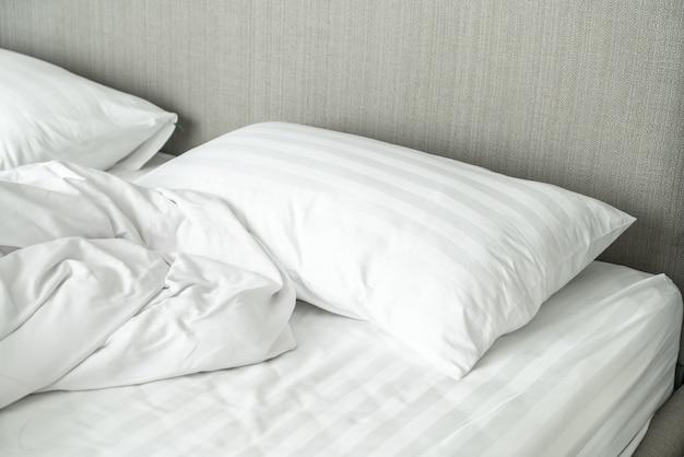 Travesseiro na cama e com cobertor bagunçado de rugas no quarto