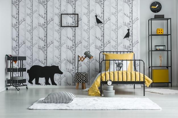 Travesseiro preto e branco com padrão houndstooth colocado no carpete no quarto infantil