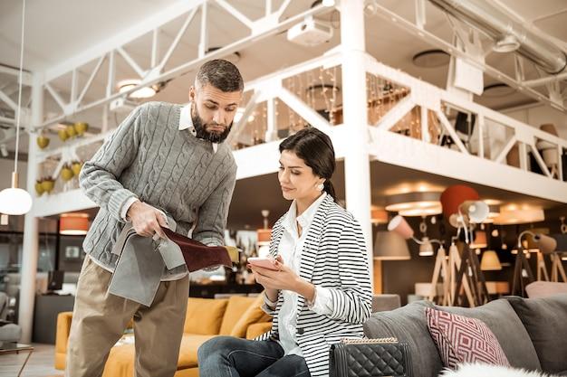 Travesseiros e materiais. homem barbudo inseguro mostrando tecido de veludo para a esposa enquanto ela está sentada com um smartphone
