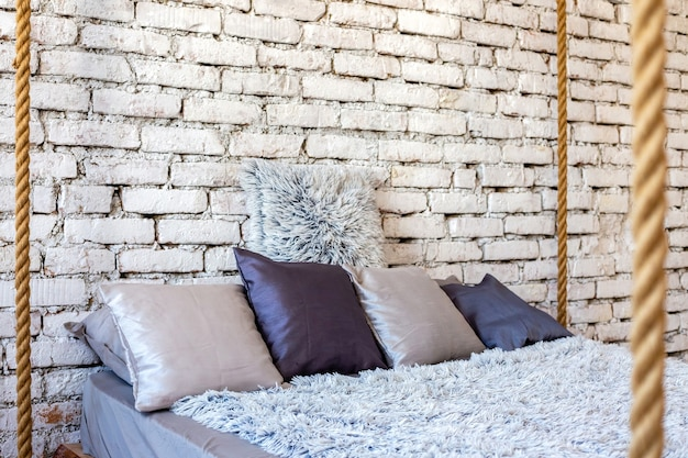 Travesseiros na cama de madeira no interior do loft de um quarto moderno e elegante.