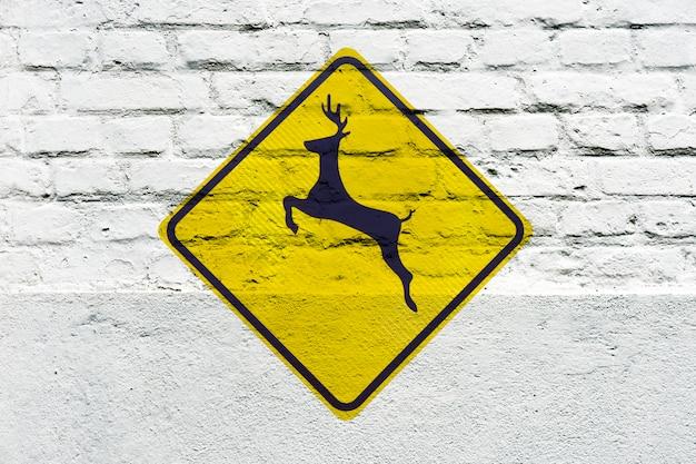 Travessia de cervos: sinal de trânsito estampado na parede branca, como um grafite