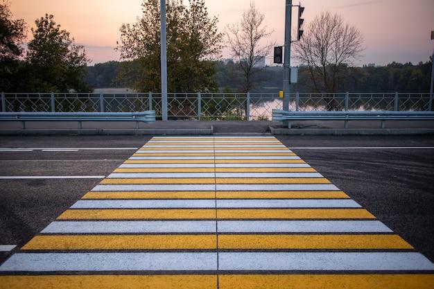 Travessia de pedestres com semáforos em estrada de asfalto