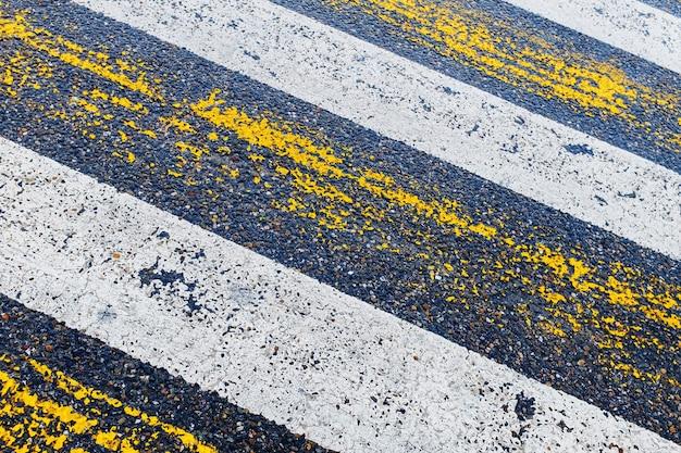 Travessia de pedestres, listras amarelas e brancas no asfalto molhado em forma de textura e substrato