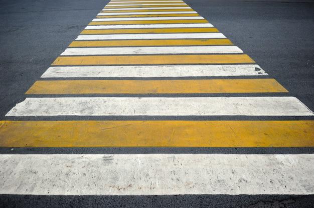 Travessia de pedestres na estrada consiste em faixas brancas e amarelas
