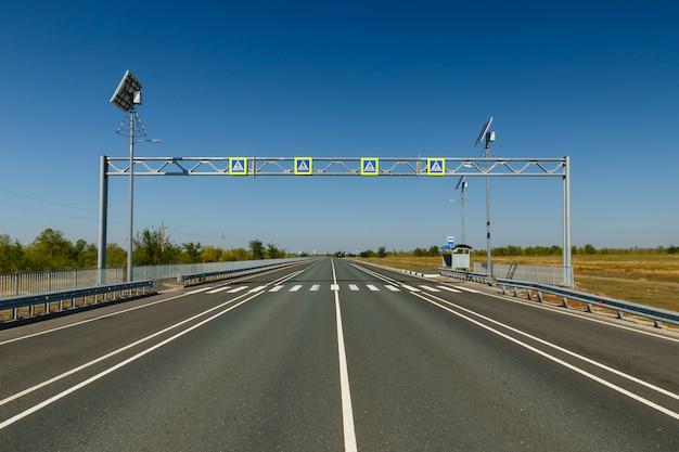 Travessia de pedestres, sinal de estrada azul com um símbolo de pedestre sobre uma estrada de asfalto