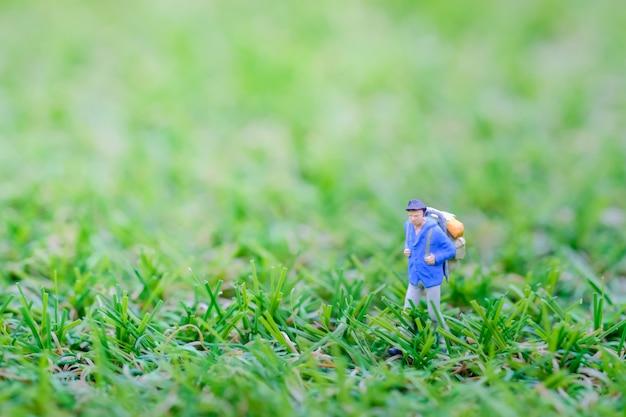 Travler figura em miniatura com mochila caminhando na grama