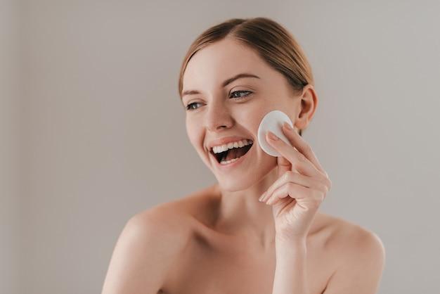 Trazendo frescor para sua pele. retrato de estúdio de uma mulher atraente limpando a pele com uma almofada de algodão em pé contra o fundo