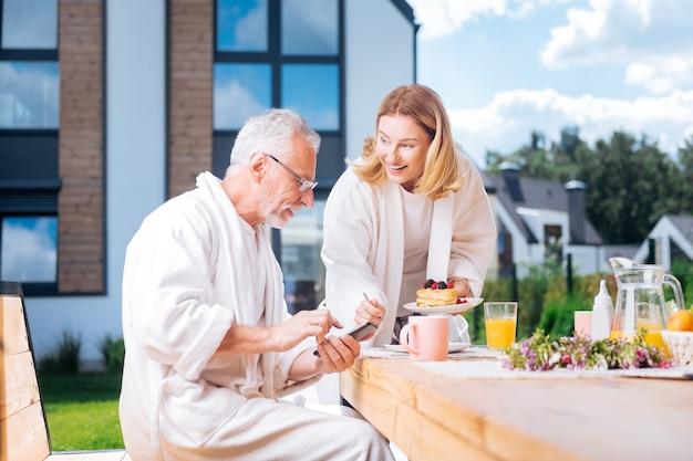 Trazendo panquecas. esposa amorosa e carinhosa usando roupão branco e trazendo panquecas com frutas, seu lindo marido