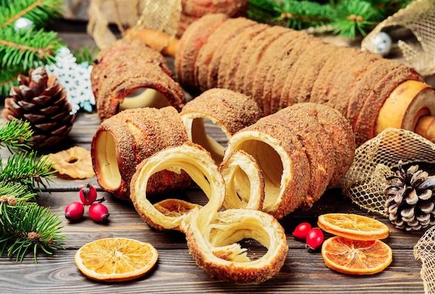 Trdelnik é uma iguaria assada no espeto e massa de carvão com açúcar, canela e baunilha. doces de natal, comida de rua. cozinha checa e da morávia.