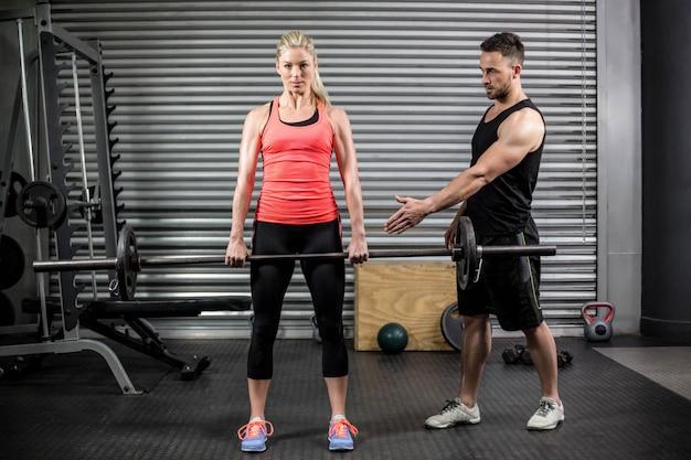 Treinador, ajudando a mulher com barra de levantamento no ginásio