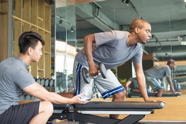 Treinador, ajudando, homem, levantamento, dumbbell, em, ginásio