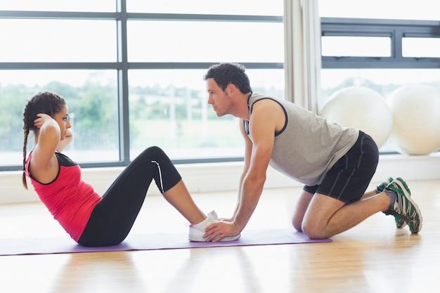 Treinador, ajudando, mulher, abdominal, crunches, em, ginásio
