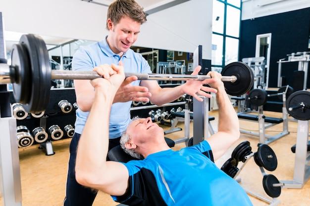 Treinador, ajudando o homem sênior, levantando a barra no ginásio