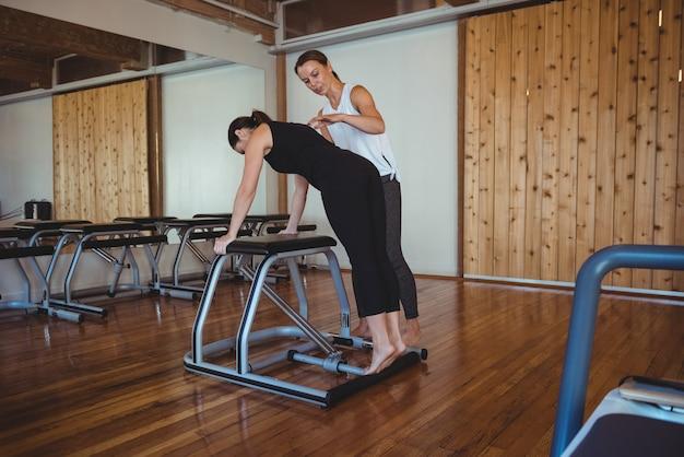 Treinador ajudando uma mulher enquanto pratica pilates