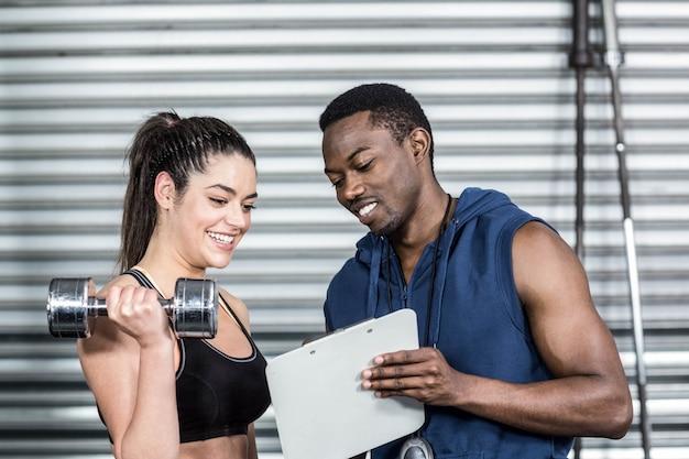Treinador atlético, explicando o plano de treino para mulher no ginásio crossfit