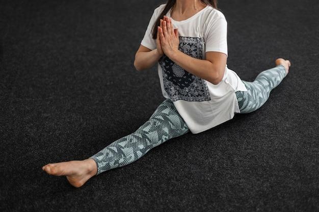 Treinador atlético jovem senta-se em um fio e medita. a menina aquece os músculos antes do treino. yoga ou alongamento é um estilo de vida esportivo saudável. fechar-se.