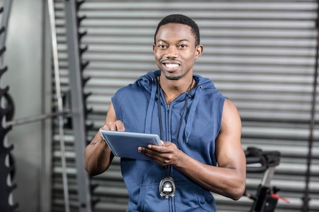 Treinador atlético usando tablet digital no ginásio crossfit
