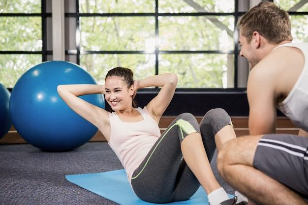 Treinador, auxiliando a mulher com abdominais