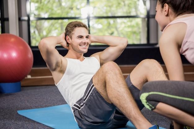 Treinador, auxiliando o homem com abdominais