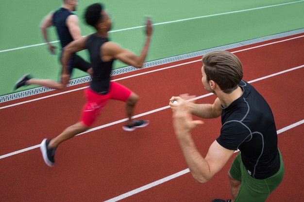 Treinador bonito gritando perto de grupo jovem atleta multiétnico