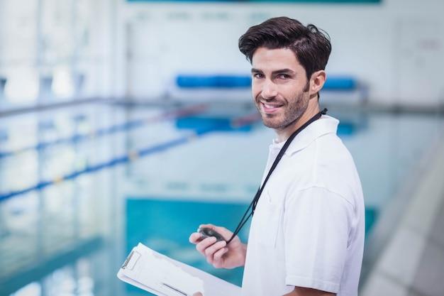 Treinador bonito segurando cronômetro e lendo a área de transferência na piscina