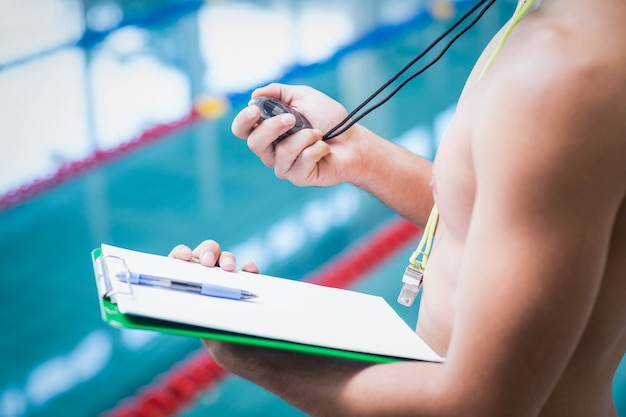 Treinador bonito segurando cronômetro e prancheta na piscina