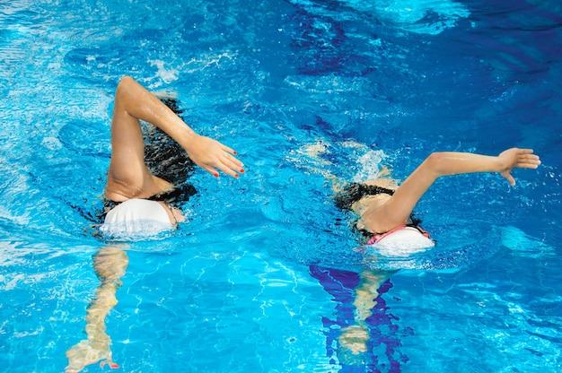 Treinador charmoso com seu aluno nadando na piscina
