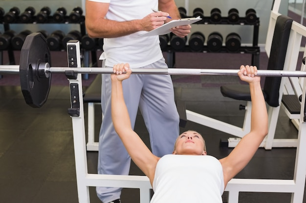 Treinador com prancheta além da mulher levantando a barra na academia