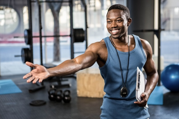 Treinador confiante mostrando o ginásio para a câmera no ginásio crossfit