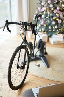 Treinador de bicicleta preto na sala com laptop e árvore de natal