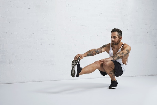 Treinador de calistenia tatuada brutalmente mostra exercícios de agachamento com uma perna, isolado na parede de tijolos brancos