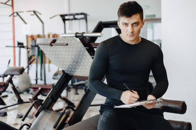 Treinador de cara jovem toma notas no ginásio. personal trainer para esportes.